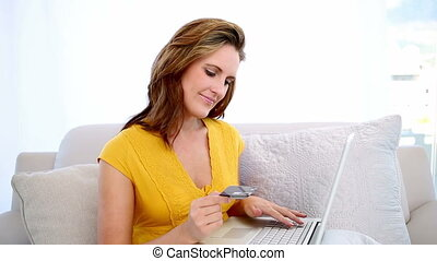Happy woman shopping online with laptop on the couch at home...