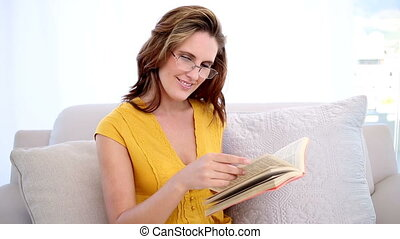 Happy woman reading a book on the c