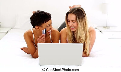 Two pretty friends shopping online lying on bed at home in...