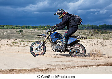 enduro - Enduro bike rider driving across the desert