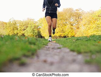 Female athlete jogging in park - Low section image of female...