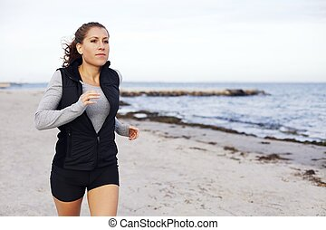 Fit and healthy woman jogging on beach Beautiful young...