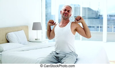 Happy man yawning and stretching sitting on bed at home in...