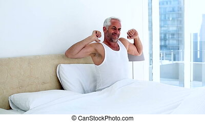 Smiling man yawning and stretching sitting on bed at home in...