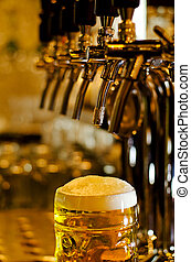 Tankard of beer with a frothy head - Close up view of a...