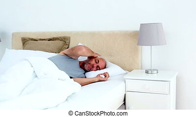 Ill man waking up and blowing his nose at home in bedroom