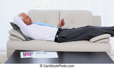 Businessman falling asleep holding paperwork on the couch in...