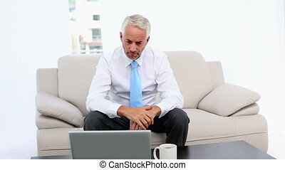 Stressed businessman looking at laptop then camera in office...