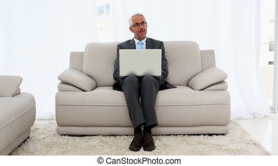 Smiling businessman using laptop on the couch in office...