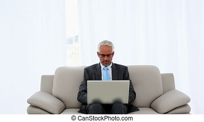 Successful businessman using laptop on the couch and...