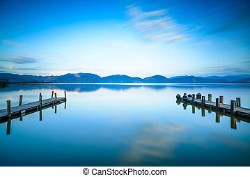 Two Wooden pier or jetty on a blue lake sunset and cloudy...