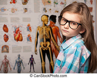 Clever pretty young girl in glasses with a serious...