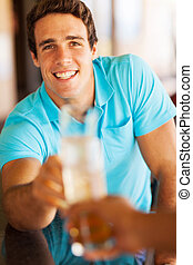 happy young man at the pub having drinks with a friend