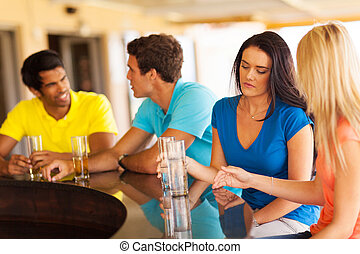 girl sitting at the bar with friends