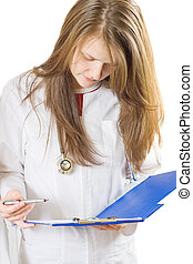 Inspecting medical chart - A young female doctor inspecting...