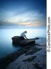 Woman sitting and contemplating alone on the rock by the...