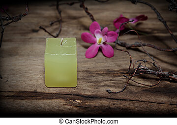 Still life yellow candle,orchids and branch on wooden board