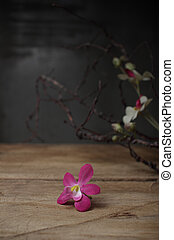 Still life artificial flower and branch on wooden board