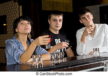Three young friends downing shots of vodka - Three young...