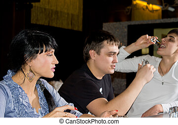 Three friends drinking shots of vodka