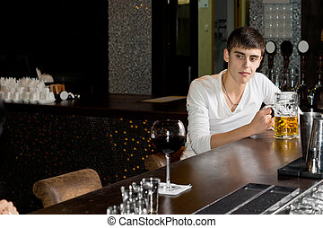 Morose drunk young man drinking beer sitting alone at the...