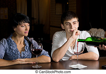 Barman pouring wine watched by a young couple