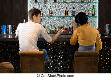 Young couple sitting drinking at the bar - View from behind...