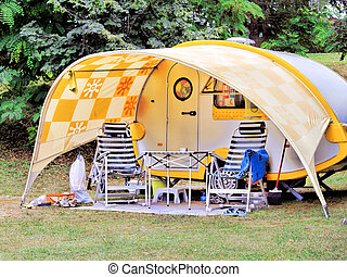 Camping - Caravan at camping site, table and empty chairs in...