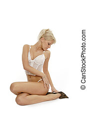 Sitting lady in lingerie with blond hair White background