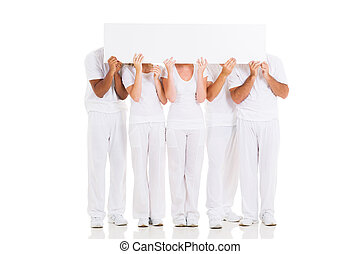 group of people hiding their faces behind white board