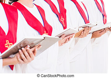 church choir holding hymn books - close up portrait of...