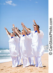church choir worshiping on beach - young church choir...
