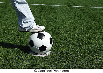 Casual guy in blue jeans stepping onto a soccer ball in...