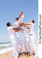 group of friends throwing a girl into air on beach