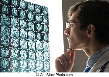 male doctor looking at the x-ray image attached to the...