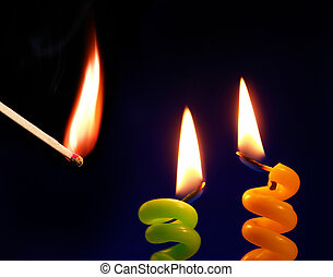 Candle and match on a black background...