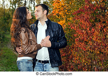 A young couple on a date in autumn park - A young couple on...