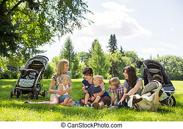 Mothers And Children Enjoying Picnic In Park - Mothers and...