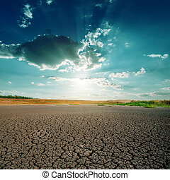 global warming. dramatic sky over cracked earth