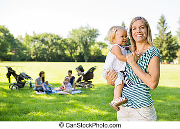 Happy Mother Carrying Daughter In Park - Portrait of happy...