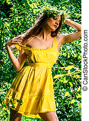 A girl in a yellow dress in the forest