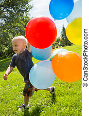 Happy Boy With Balloons Walking In Park - Full length of...