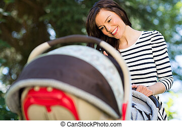 Mother Looking Into Baby Carriage In Park - Beautiful young...