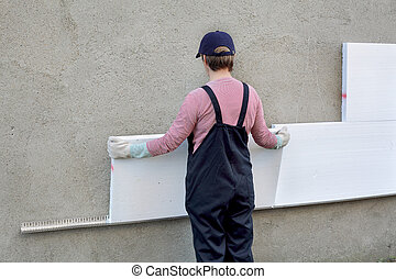 Styrofoam insulation - Female worker placing styrofoam sheet...