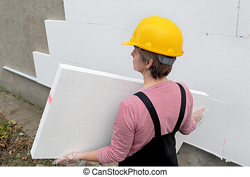 Styrofoam insulation - Female worker carry styrofoam sheet...