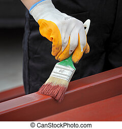 Home renovation - Worker painting steel tube with paint...