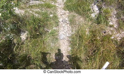 Cyclist carrying his bike uphill on steep mountain path...