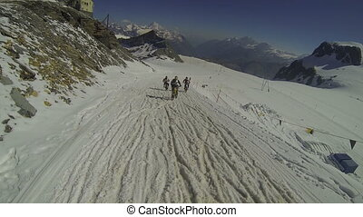 Cyclists going downhill on snow