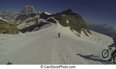 Cyclists going downhill on snow - Cyclists going downhill on...