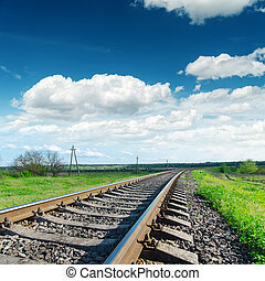 low view to railroad under cloudy sky